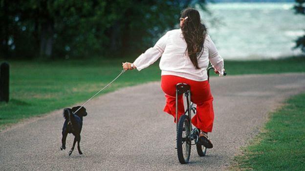 Una mujer en una bicicleta acompañada de un perro
