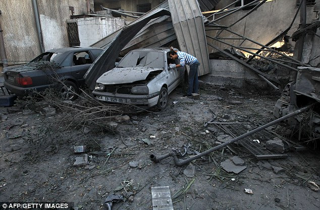 Blown out: A Palestinian man looks at a damaged vehicle parked outside a destroyed branch of the Islamic National Bank following an Israeli air strike in Gaza City
