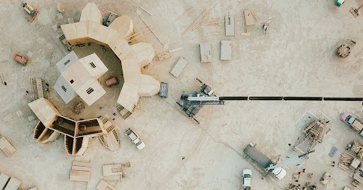 unreal aerial photos of the burning man building process, by shalaco sching