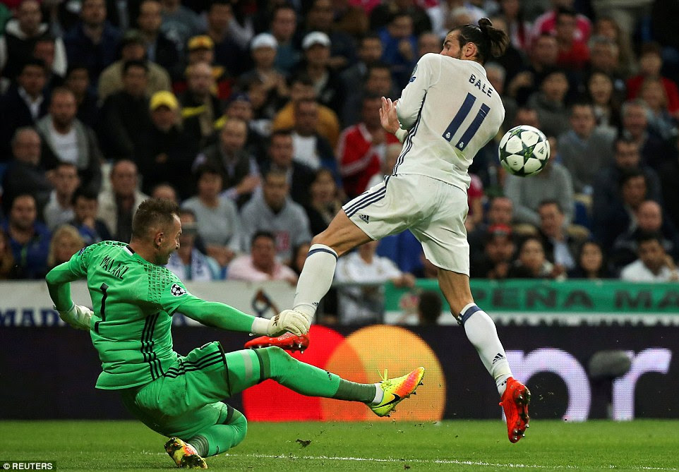 Bale putsMalarz under pressure as the Polish side's goalkeeper attempts to make a clearance whilst on the slide