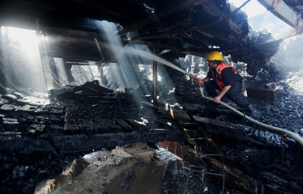 A Palestinian firefighter hoses a boat hit in an missile strike at the port in Gaza City.