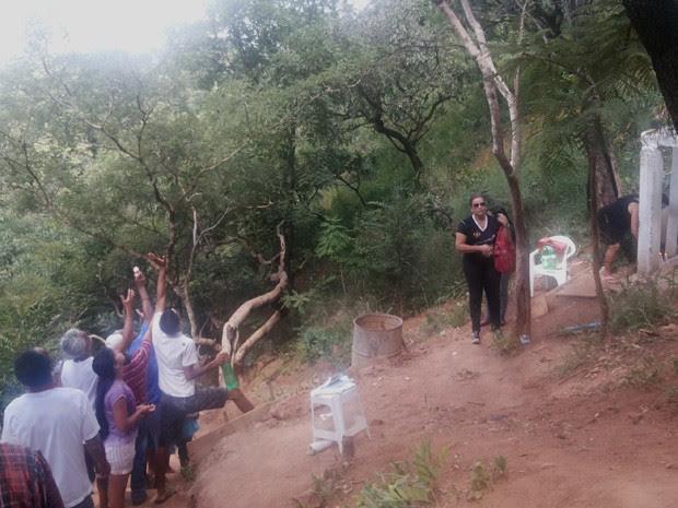 Fiéis tentam ser atingidos por gotas que pingam de árvore 'milagrosa' em condomínio no Sol Nascente, em Ceilândia (Foto: Isabella Formiga/G1)