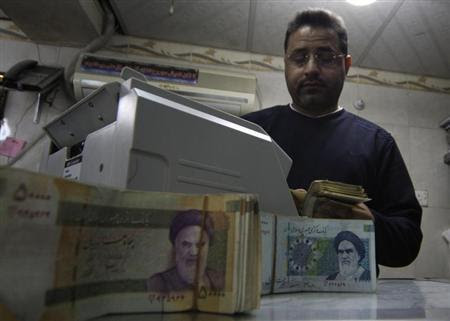 A man counts stacks of Iranian rials at a currency exchange shop in Kerbala , 110 km (70 miles) south of Baghdad January 23, 2013. REUTERS/Mushtaq Muhammed