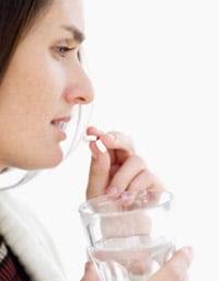 Perfil de mujer joven tomando una pastilla