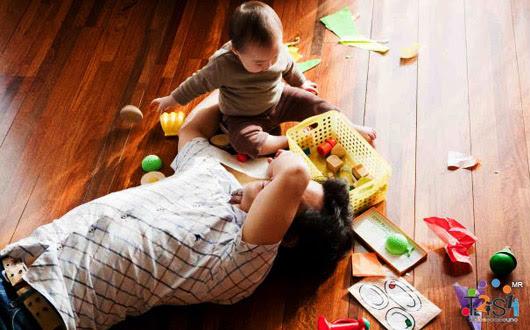 Papa acostado y bebé jugando