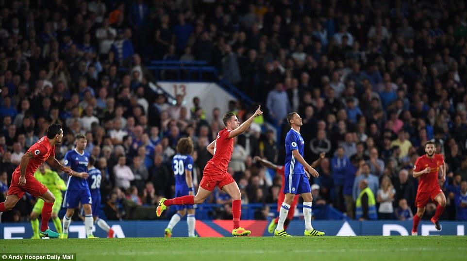 Henderson wheels away in celebration as Chelsea defenders look away in the background