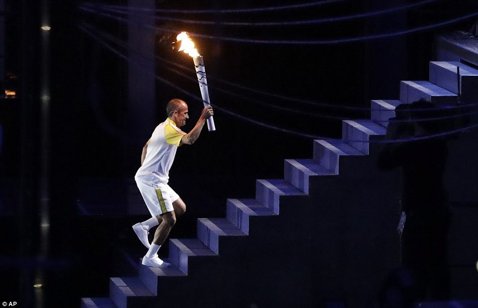 The Brazilian marathon runner, de Lima, carries the Olympic flame up the stairs towards the cauldron during the opening ceremony