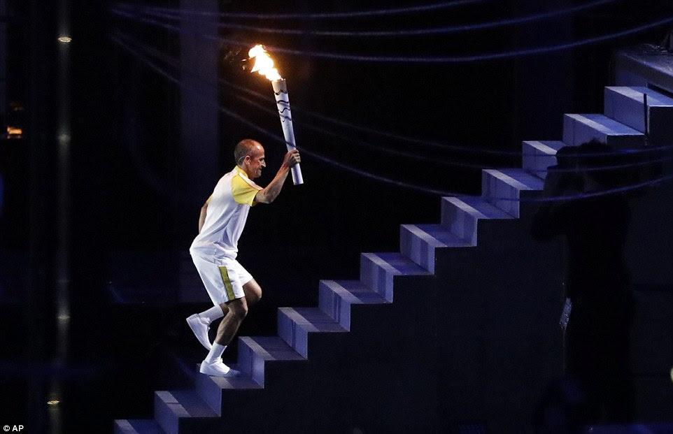 O maratonista brasileiro, de Lima, carrega a chama olímpica até as escadas em direção ao caldeirão durante a cerimônia de abertura