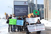 """Students holding placards in front of """"Queen's University"""" sign"""