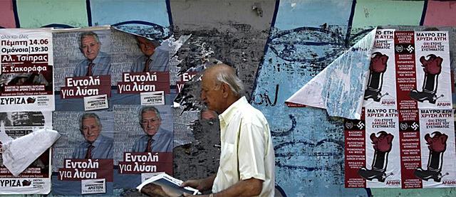 Finaliza la campaña electoral en Grecia. Un hombre camina con los cartes de fondo. | Efe