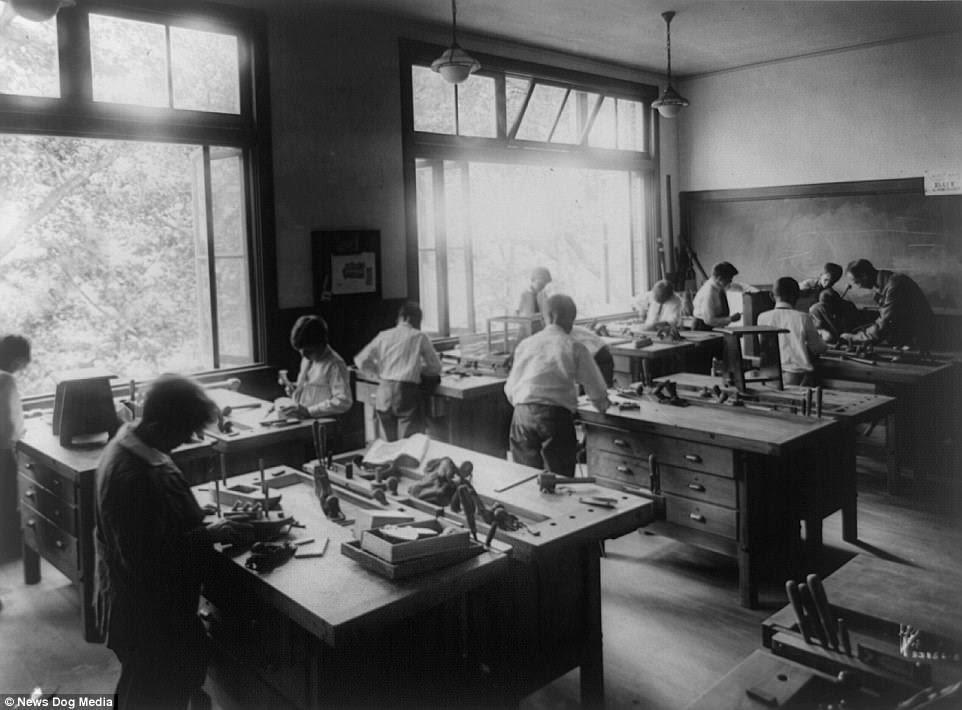 School boys are captured studying carpentry at Riverdale Country School in New York City with the windows wide open, circa 1910s