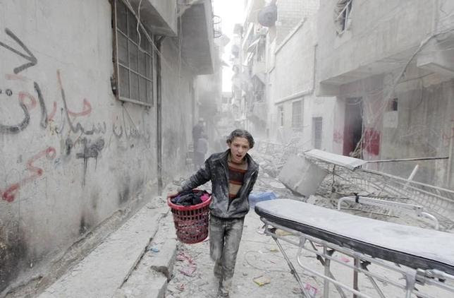 A boy carries his belongings at a site hit by what activists said was a barrel bomb dropped by forces loyal to Syria's President Bashar al-Assad in Aleppo's al-Fardous district, Syria April 2, 2015. REUTERS/Rami Zayat