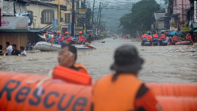 Rescuers maneuver down a flooded street as they evacuate residents in the village of Tumana in suburban Manila on Tuesday, August 7, after torrential rains inundated most of the capital. Authorities have issued a red alert for the metropolitan Manila area. Downpours are expected to continue Wednesday.