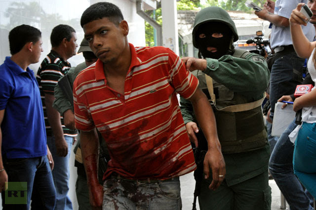 A member of the Venezuelan army leads a prisoner wounded during a riot in the Uribana prison, in Barquisimeto, Lara state, Venezuela, on January 25, 2013.(AFP Photo / Dedwinson Alvarez-Diario el Impulso)