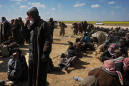 Heads bowed to the ground, suspected IS members surrender