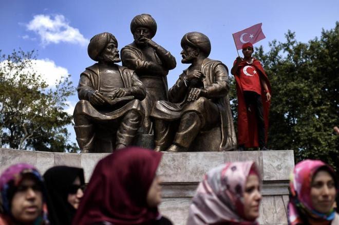 Un niño con una bandera turca junto a la estatua del sultán Mehmed II