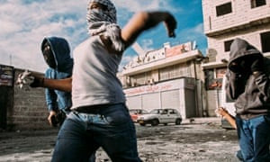 Palestinian youth throw stones at Israeli forces during a clash at the entrance to Shuafat refugee camp in Jerusalem in 2014. 2014, a year characterised by an EU report as the violent and polarised in the city in recent memory.