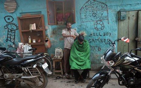 A man cuts hair near the residential complex where Badar Azim lives