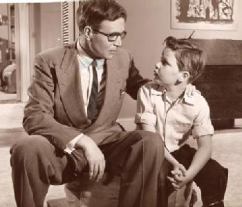 A stern 1950s dad with horn-rimmed glasses sits next to his son.