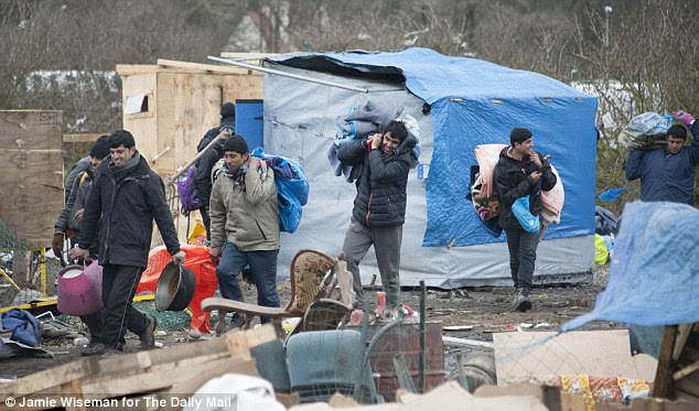 Migrants are pictured here moving their possessions out of the southern half of the camp ahead of its demolition