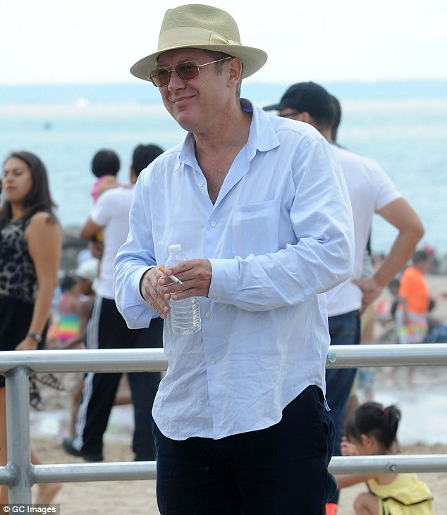 Sneaky smoke: The actor held a cigarette and a bottle of water as he mingled with holidaymakers during filming