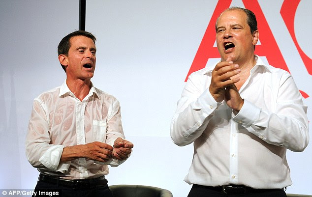 First secretary of the French left-wing Socialist Party Jean-Christophe Cambadelis (right) and French Prime Minister Manuel Valls applaud after Valls delivered his speech