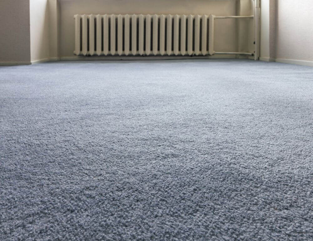 Interior close-up photo of blue carpet floor and heater on the background