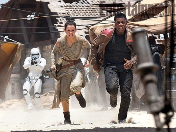 First Order stormtroopers take aim at Rey (Daisy Ridley) and Finn (John Boyega) as they run away in this production still for STAR WARS: THE FORCE AWAKENS.