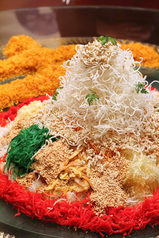 The towering yusheng is sprinkled with gold dusted rice crispies