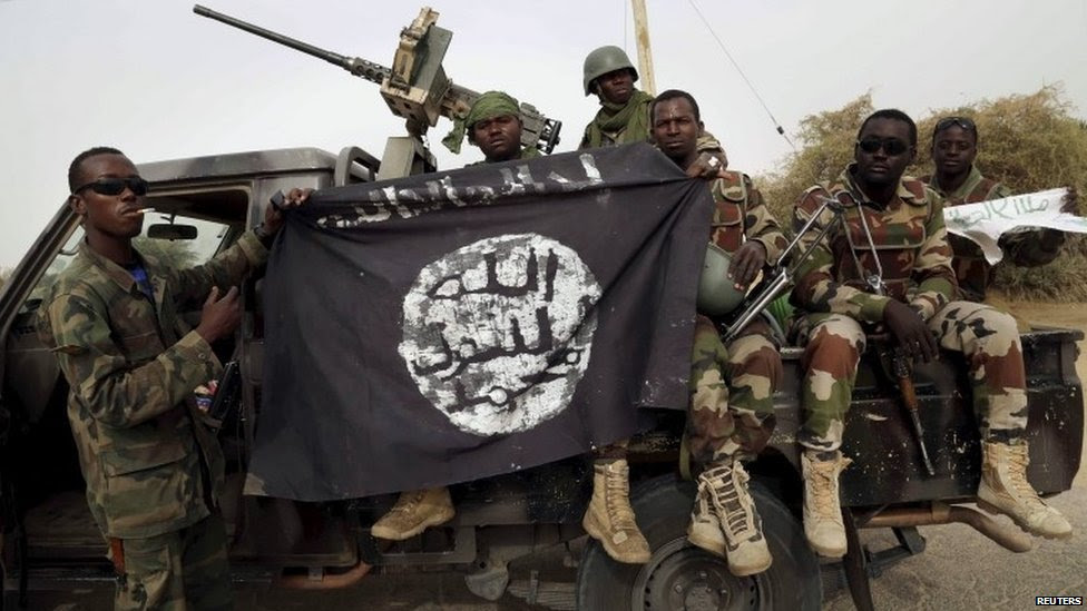 Nigerien soldiers hold up a Boko Haram flag that they had seized in the recently retaken town of Damasak, Nigeria, 18 March  2015