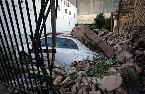 Chile Earthquake: A car is seen under a pile of rubble in Valparaiso