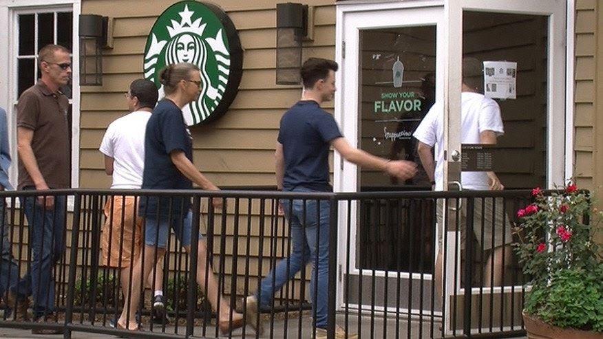 Trump supporters enter a Starbucks in Charlotte, North Carolina on June 24, 2017 for a sit-in after they said a woman was mocked for wearing a shirt supporting the president.