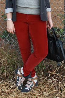 '80s hipster outfit: red corduroys by Pilcro, sneaker wedges, gray sweatshirt, gray blazer, knubbly loop scarf from anthropologie green wool hat from Topshop, studded-bottom bag