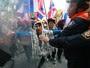 Agentes de segurança da Tailândia tentam conter manifestantes durante protesto  contra o governo em frente ao Departamento de Investigação Especial em Bangcoc. Na semana passada,  o órgão decidiu congelar as contas bancárias dos líderes dos protestos