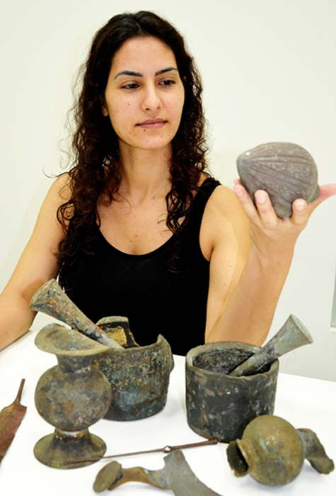 An Israel Antiquities Authority employee examining the finds.