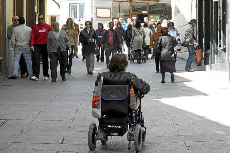 Una mujer pasea en silla de ruedas en medio de una calle peatonal.   R. Blanco