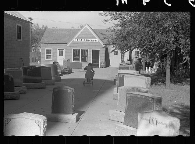 Girl playing among tombstones, Lexington, Nebraska