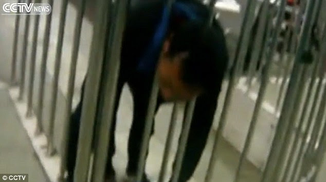 Stuck: The man became entangled in the barriers of a train station after he ran at them in Jiangxi province