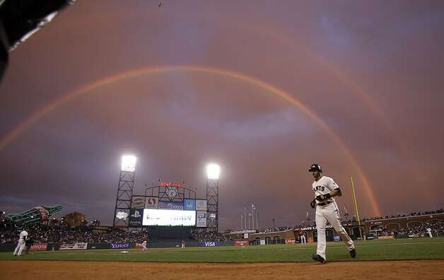San Francisco Giants' Marco Scutaro, right, walks back to the dugout after an at-bat against the Arizona Diamondbacks as a rainbow appears in the sky during the first inning of a baseball game on Wednesday, Sept. 5, 2012, in San Francisco. Photo: Marcio Jose Sanchez, Associated Press / SF