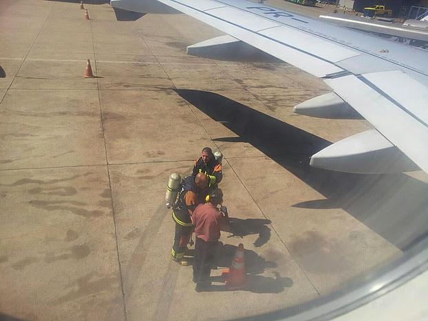 Funcionários do aeroporto do Brasília com extintores sob asa de avião que pousou na manhã desta segunda-feira (11) após material queimado ser encontrado em dois banheiros da aeronave  (Foto: Rodrigo Viellas/Vc no G1)