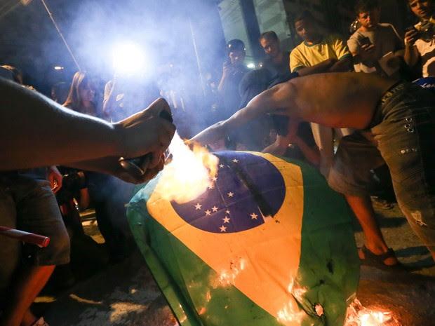 Manifestantes queimam bandeira do Brasil durante protestos contra a Copa do Mundo em São Paulo neste sábado (31) (Foto: Daniel Teixeira/Estadão Conteúdo)
