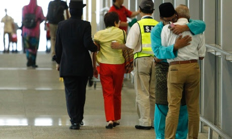 A man whose family was onboard Malaysia Airlines MH17, consoles another man who had just arrived with his wife to receive confirmation that their daughter's family was onboard the plane, at Kuala Lumpur International Airport.