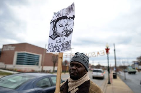 A protester held up a sign with a drawing of Michael Brown in Ferguson, Mo., on Monday.