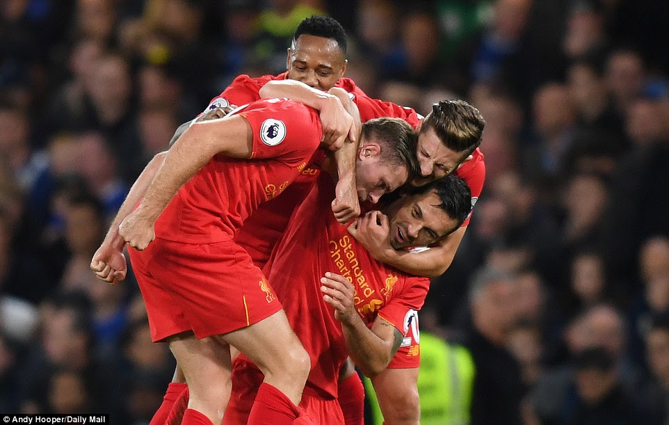 England international Henderson (front) is swamped by team-mates (L-R) Nathanial Clyne, Lallana and Lovren