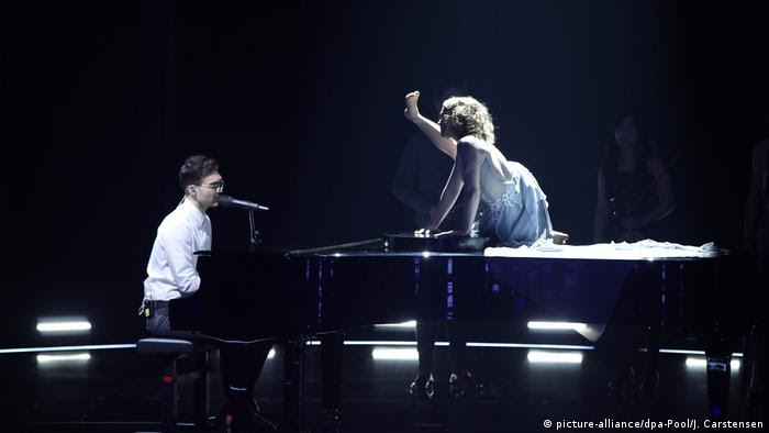 Ryk at the piano and a dancer in a white dress on it, performing at the ESC German national final (picture-alliance/dpa-Pool/J. Carstensen)