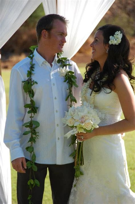 Groom wears maile lei with a single flower boutonniere