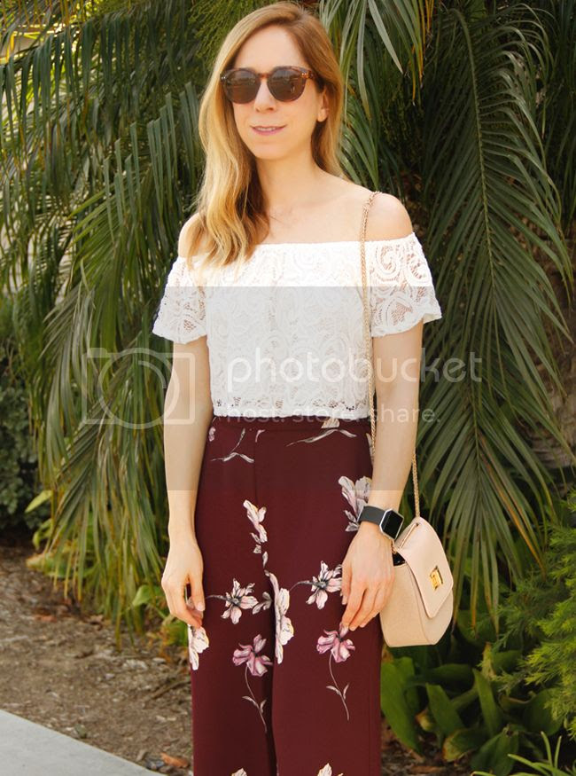 Los Angeles fashion blogger The Key To Chic wears an off the shoulder lace blouse, LC Lauren Conrad floral flare pants, and Who What Wear Collection crossbody saddle bag