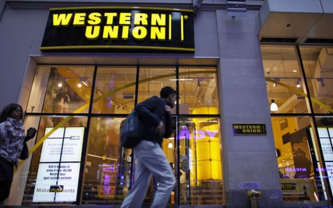 People walk past a Western Union branch at Times Square in New York November 30, 2011. REUTERS/Eduardo Munoz (UNITED STATES - Tags: BUSINESS LOGO)