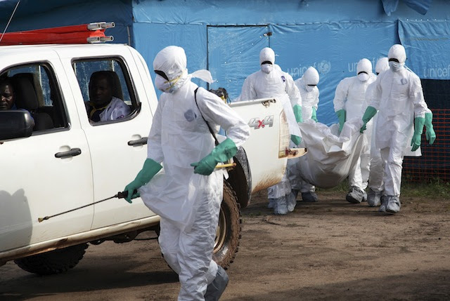 A photograph made available 27 July 2014 shows Liberian health workers in protective gear on the way to bury a woman who died of the Ebola virus from the isolation unit in Foya, Lofa County, Liberia, 02 July 2014. Ahmed Jallanzo/EPA