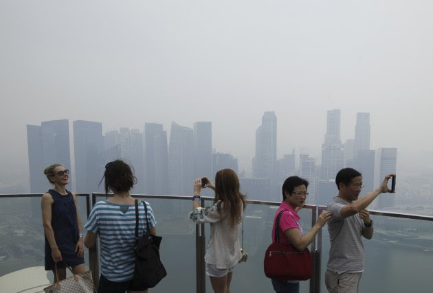 Visitors take photos at an observation deck of Marina Bay Sands Skypark overlooking the haze covered skyline of Singapore